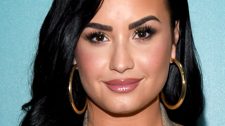 Demi Lovato with slight smile and hoop earrings