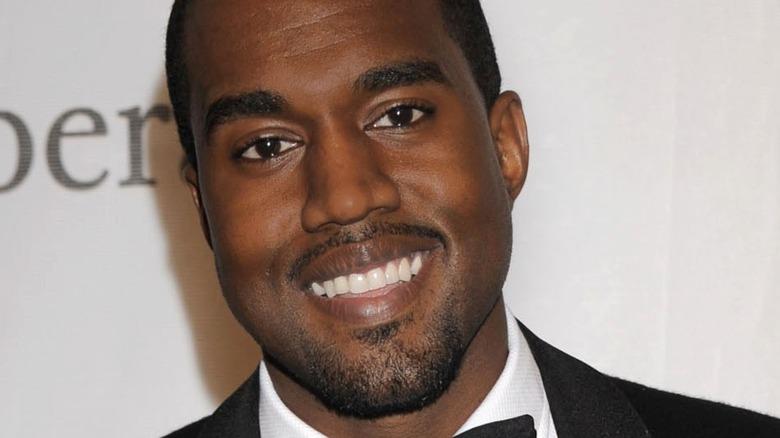 Kanye West smiles, wearing a tuxedo