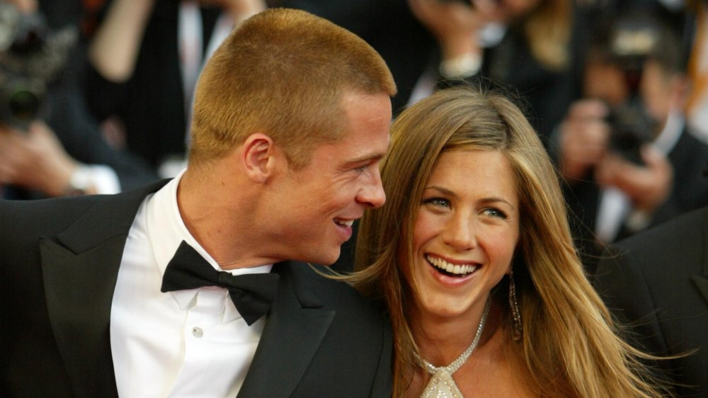 Brad Pitt and Jennifer Aniston holding hands and laughing at the Troy premiere in 2004