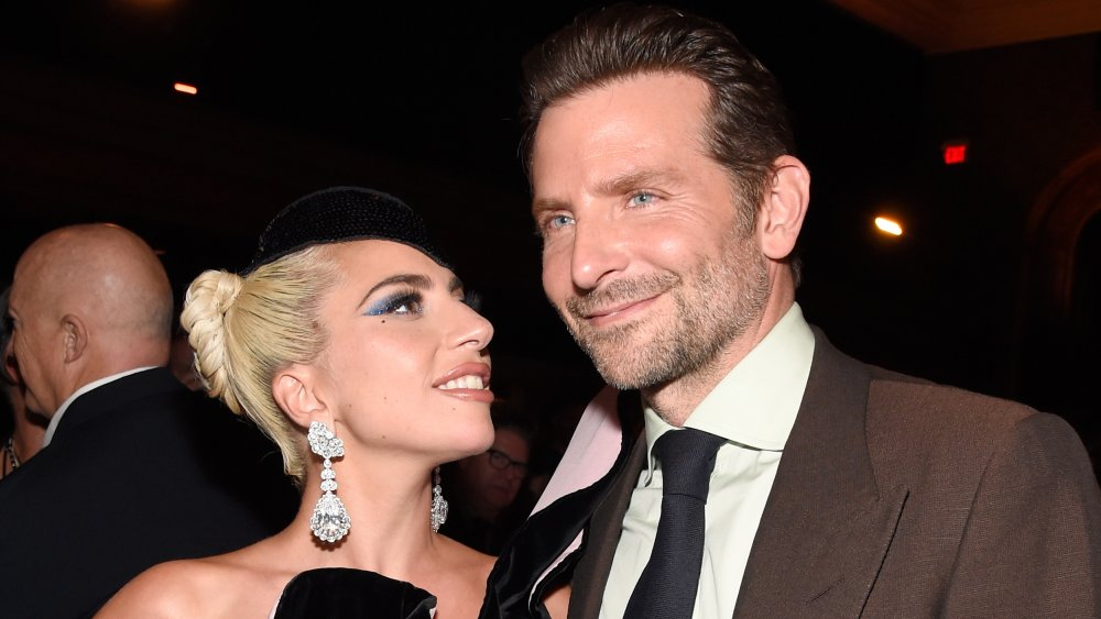 Lady Gaga in a black dress and hat, smiling and looking at a grinning Bradley Cooper