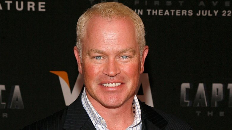 Neal McDonough wearing a black pin-striped suit with a white-and-blue checkered shirt, smiling at a movie premiere