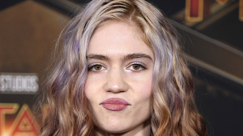 Grimes with lips pressed together