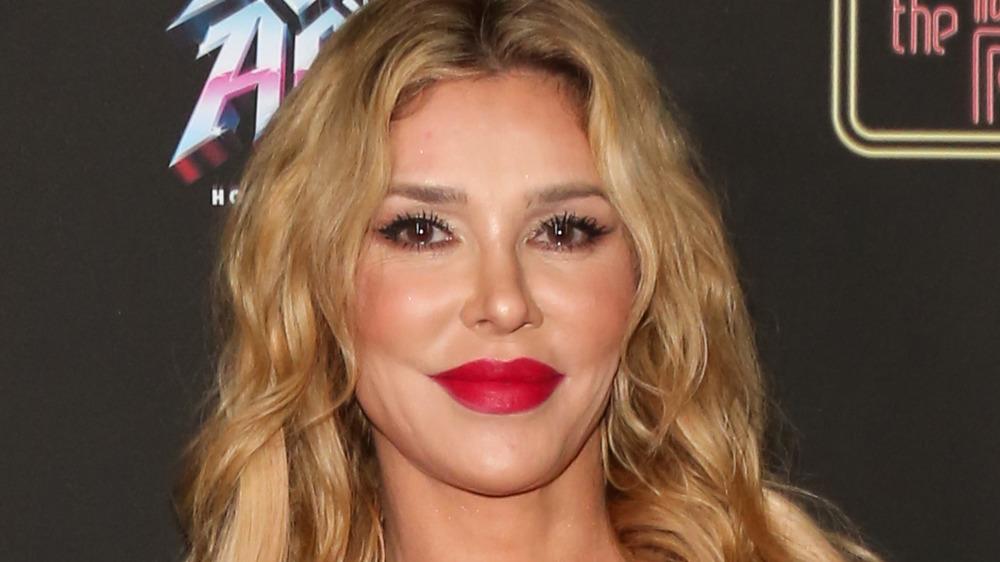 Brandi Glanville, smiling, red lipstick, blond hair down, leopard jacket, red carpet 2020