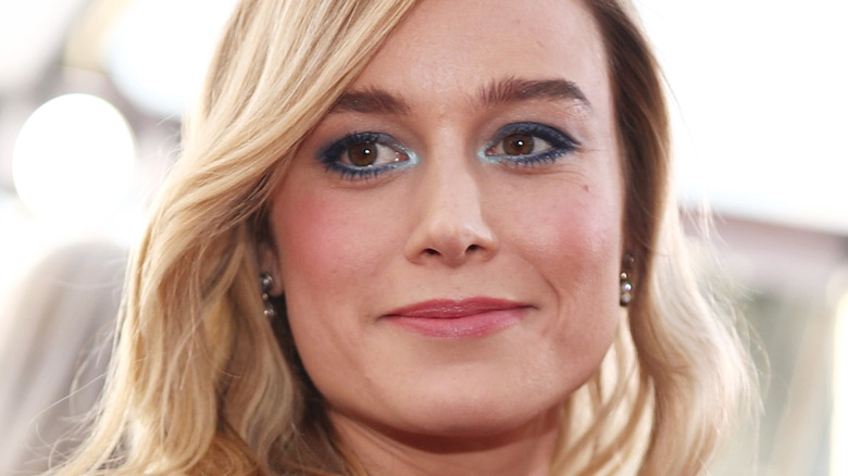 Brie Larson gives a slight smile on the red carpet