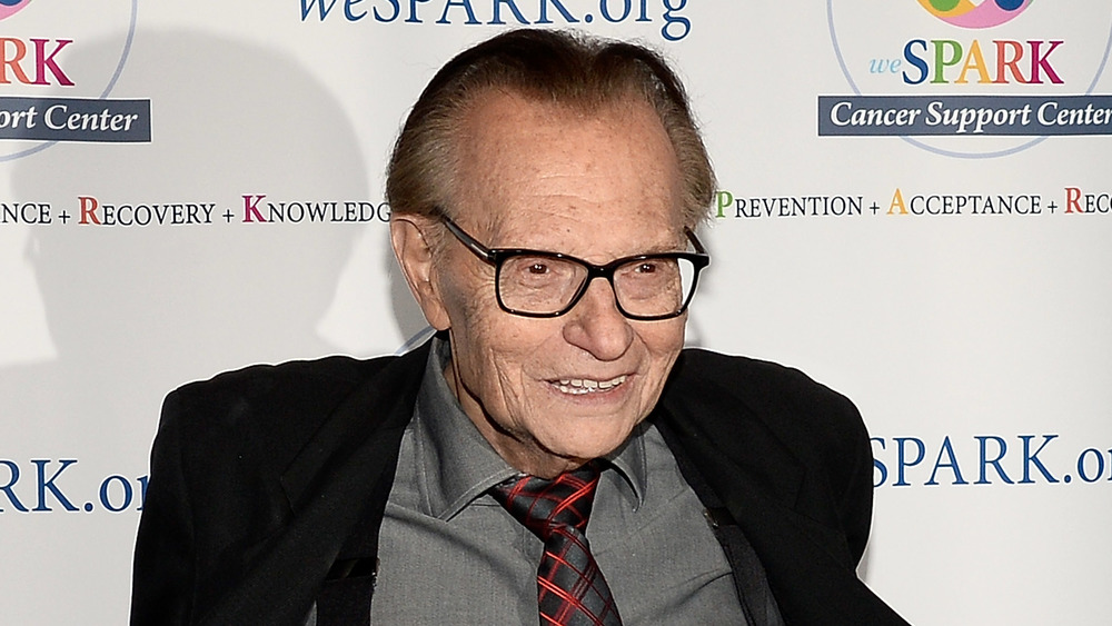Larry King smiling in suit