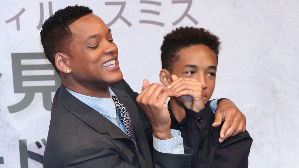 Will Smith next to Jaden Smith form a heart with their hands together