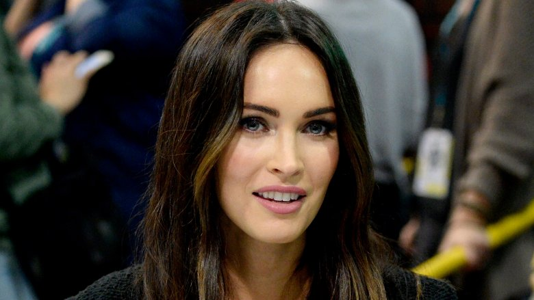 Megan Fox at a table for a fan event