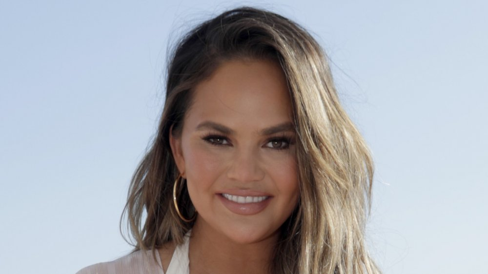 Chrissy Teigen in a white dress and gold hoop earrings, smiling on the beach