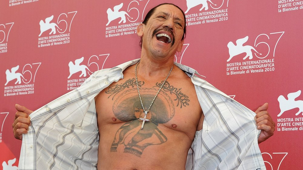 Danny Trejo baring his chest at a photocall for Machete during the 67th Annual Venice Film Festival