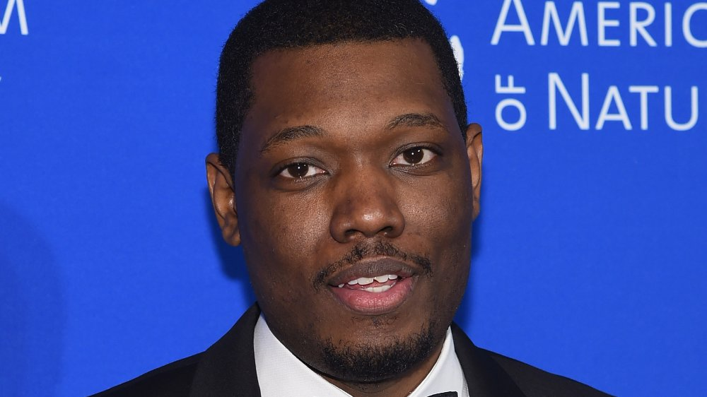 Michael Che in a black tux, posing at a museum event