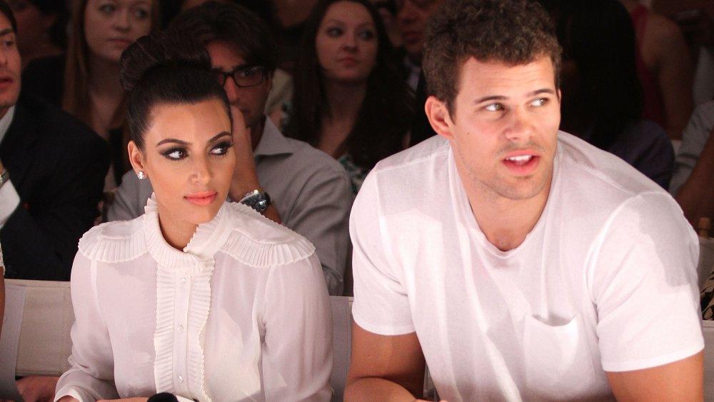 Kim Kardashian and Kris Humphries sitting next to each other