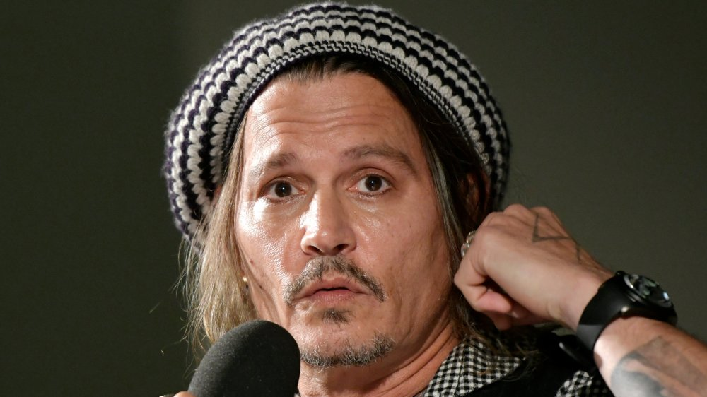 Johnny Depp wearing a black-and-white knitted hat, looking shocked while speaking into a mic