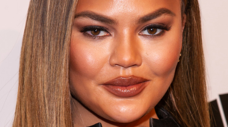 Chrissy Teigen with a neutral expression