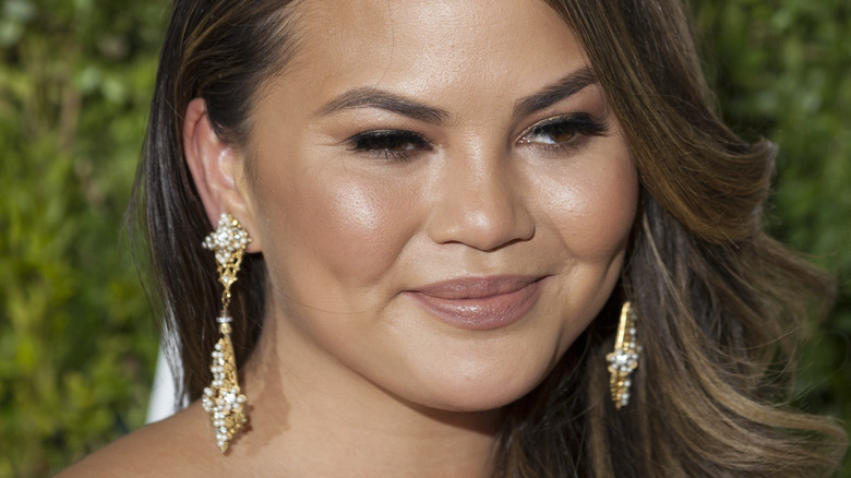 Chrissy Teigen smiling and looking to the side at Tony Awards 2017