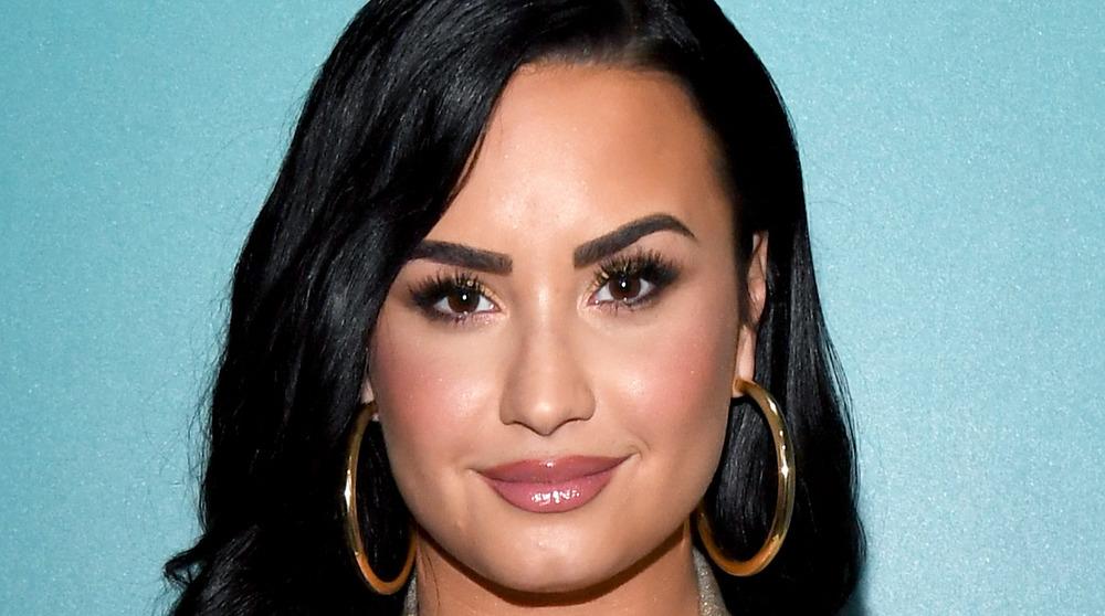 Demi Lovato smiling while wearing hoop earrings