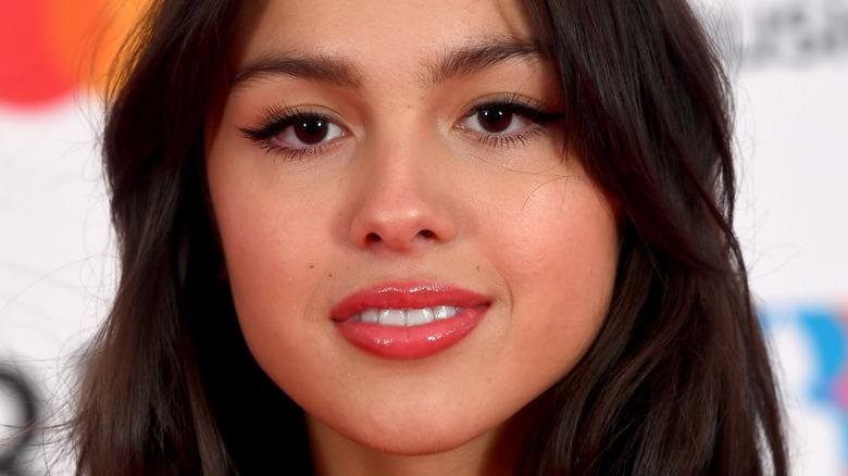 Olivia Rodrigo smiling at camera with cat eye makeup