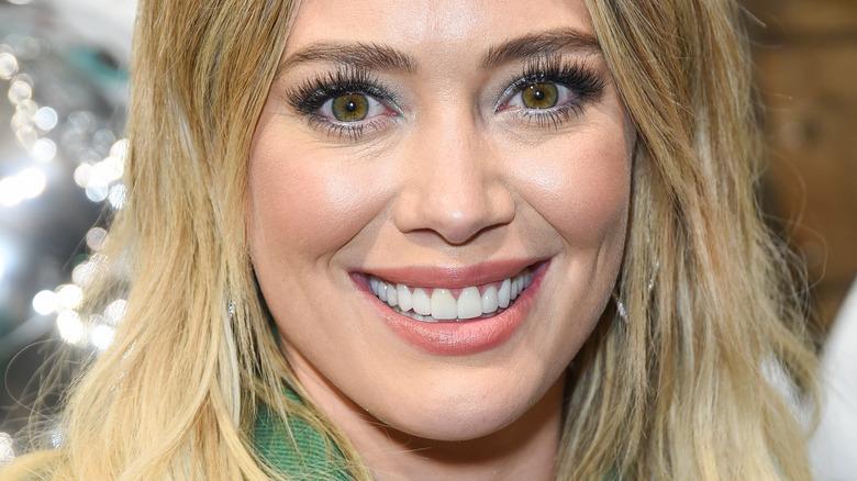 Hilary Duff, smiling, wearing blond hair down, green blazer, 2019 event