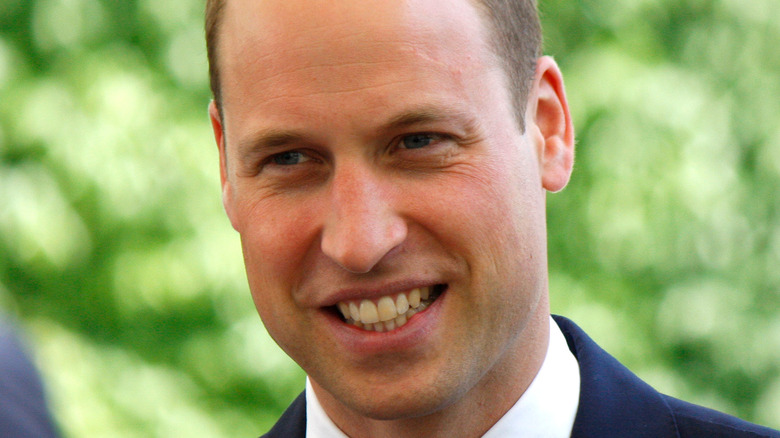 Prince William smiles in a navy suit.