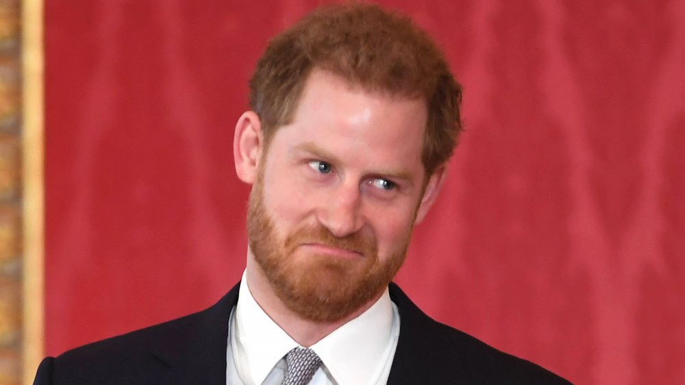 Prince Harry shrugging and pulling a face in a dark blue suit