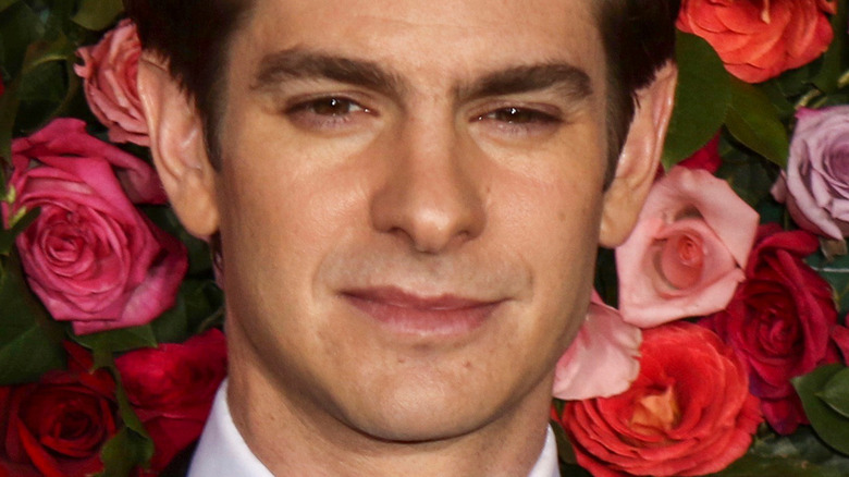 Andrew Garfield with serious expression in front of floral background