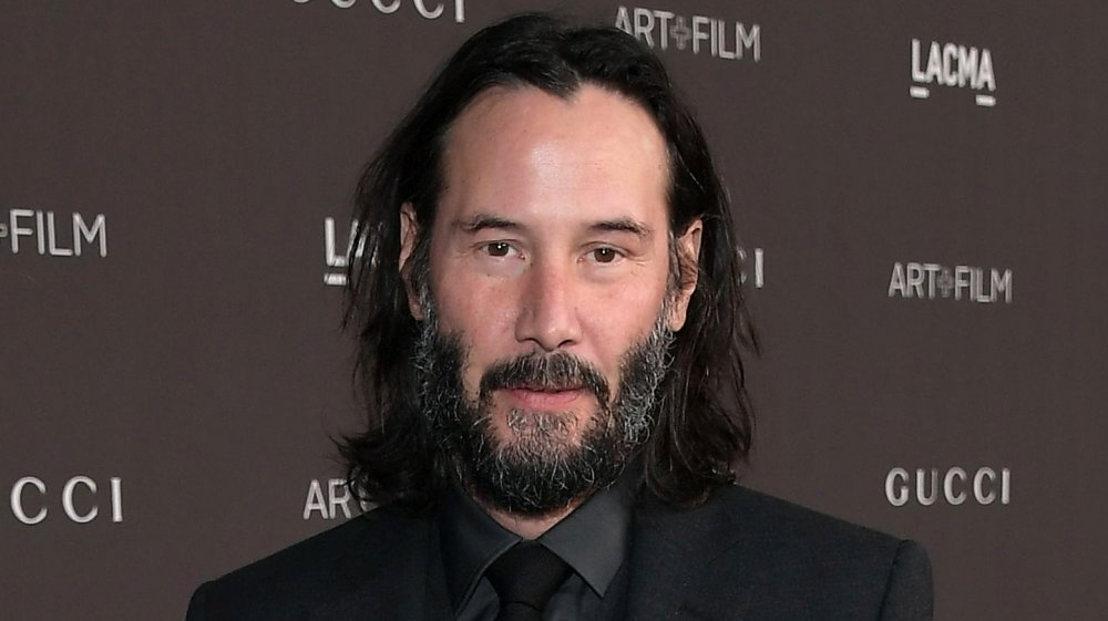 Keanu Reeves in a black three-piece suit, with longer hair tucked behind his ears, looking straight at the camera with a small smile