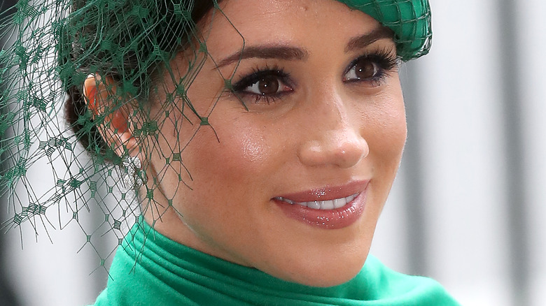 Meghan Markle smiling in green fascinator