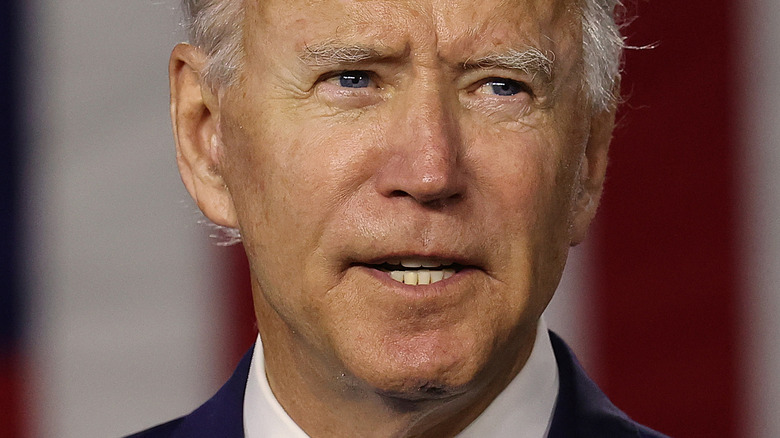 Joe Biden with serious expression in front of American flag