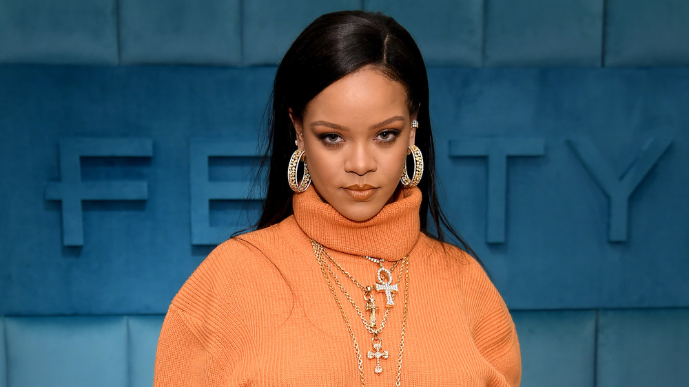 Rihanna orange sweater and jewelry