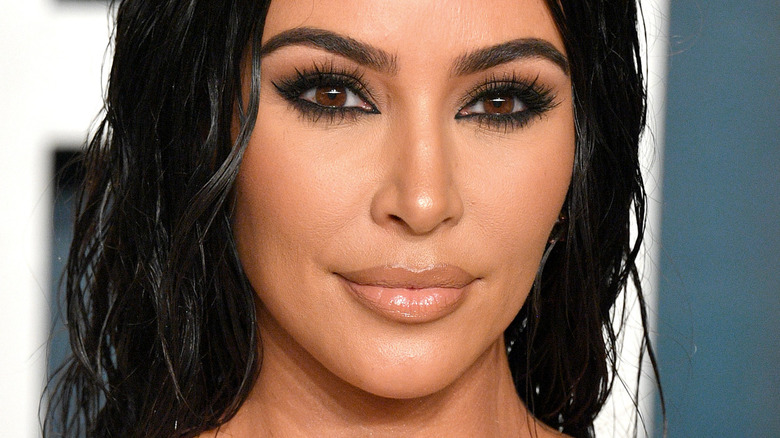 Kim Kardashian smiling and wearing heavy black eyeshadow