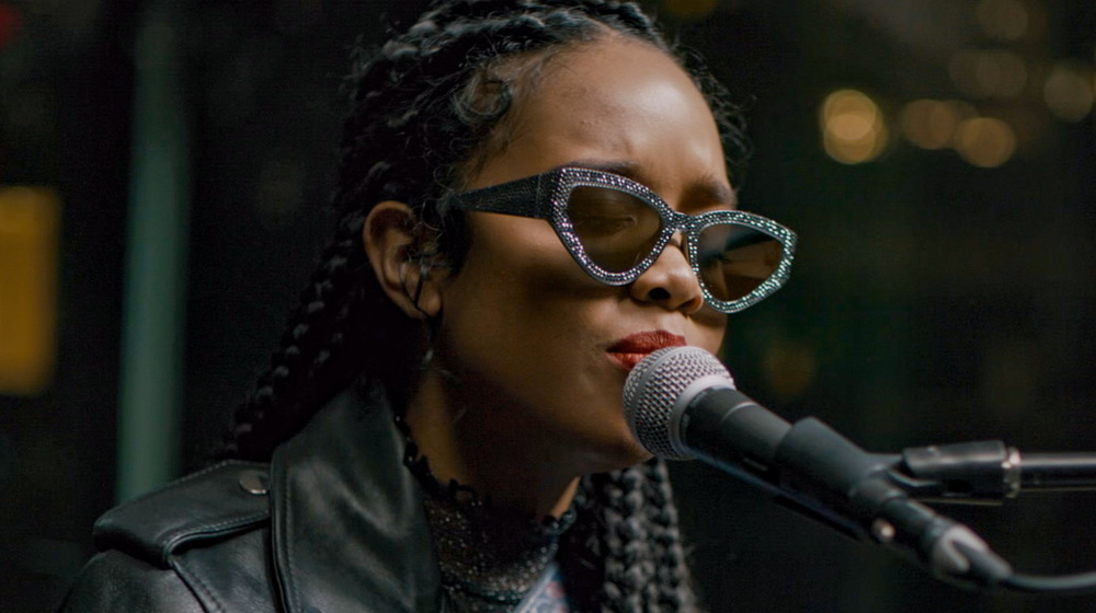 H.E.R. singing into microphone