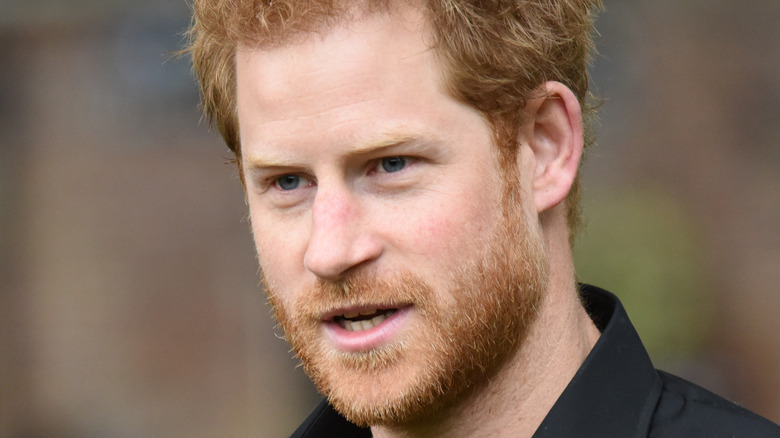 Prince Harry stands outside