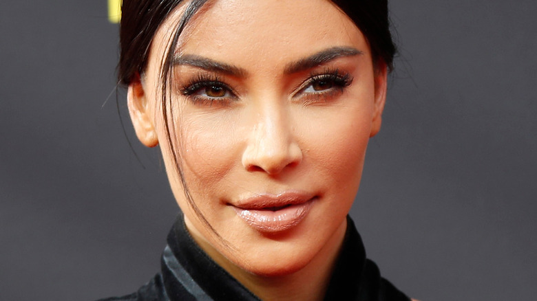 Kim Kardashian poses in a black outfit with slight smile