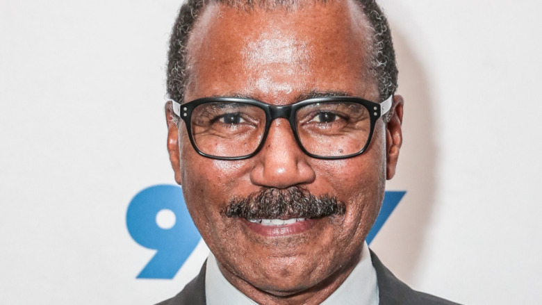 Bill Whitaker smiling wearing thick-rimmed glasses