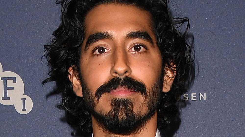 Dev Patel looks serious as he poses at an event