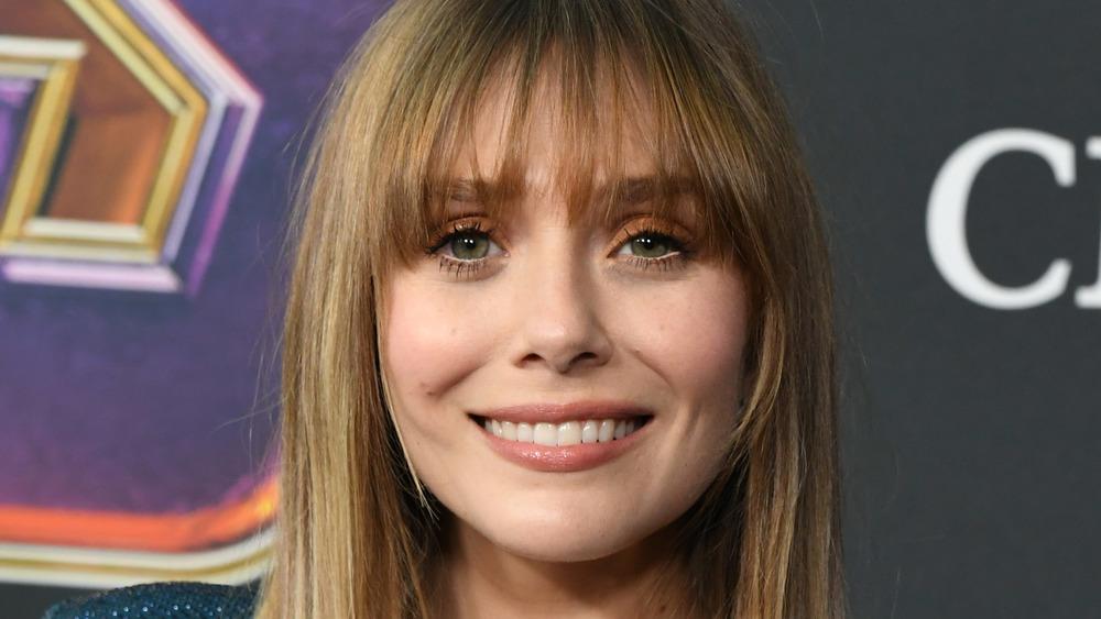 Elizabeth Olsen smiles while posing on the red carpet