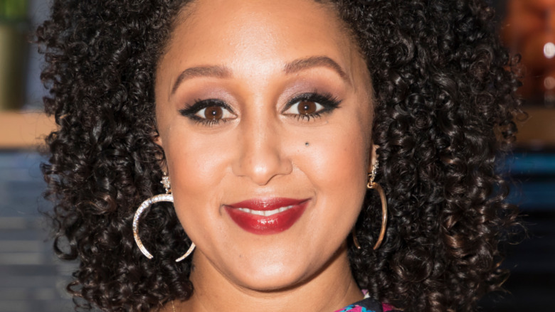 Tamera Mowry smiling with curly hair
