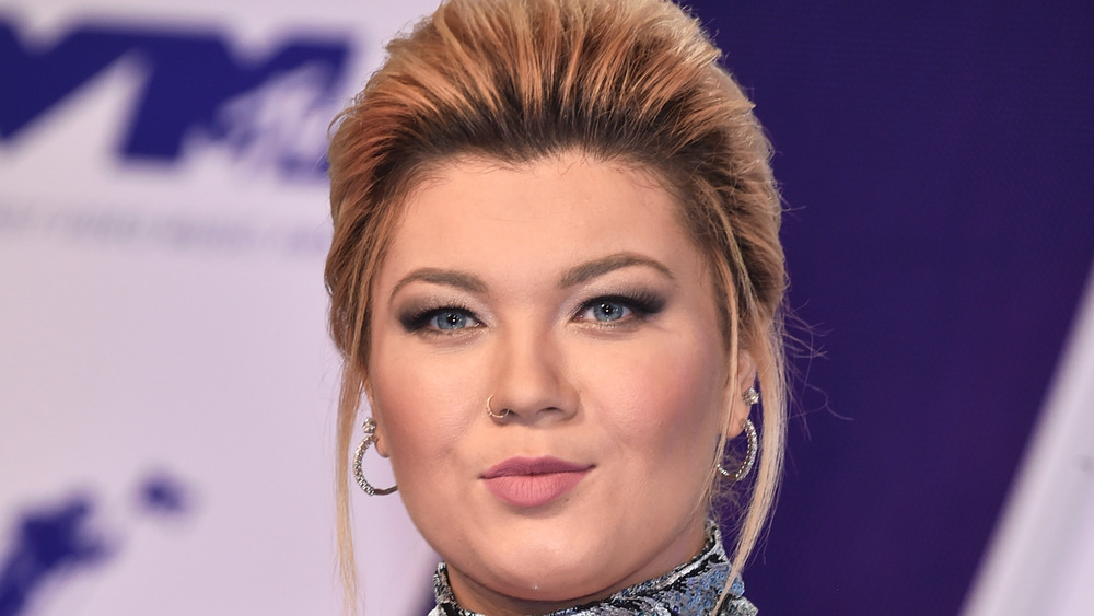Amber Portwood poses on the red carpet with her red hair in an up-do