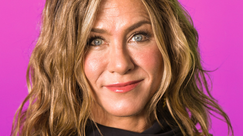 Jennifer Aniston smiling in front of a pink wall