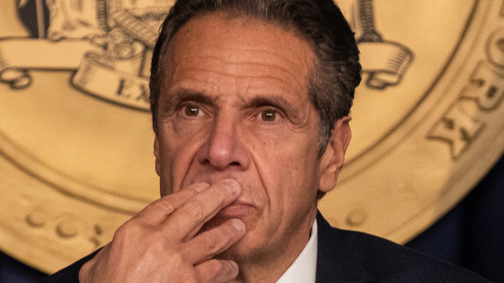 Andrew Cuomo looking on with hand on his mouth.