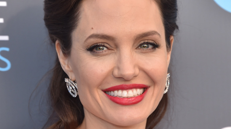 Angelina Jolie smiles in red lipstick
