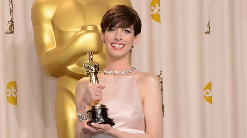 Anne Hathaway holding her Oscar award in 2013