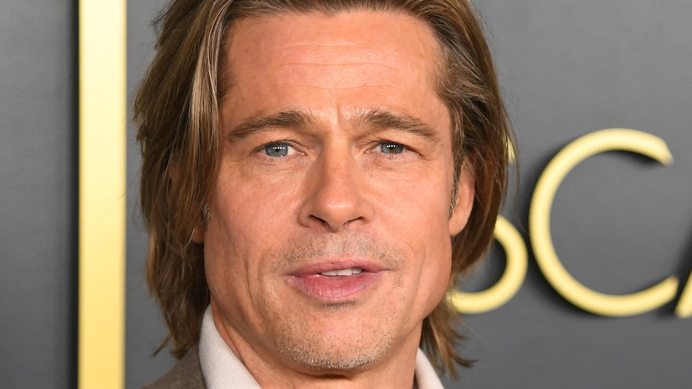 Brad Pitt posing on the red carpet with long hair