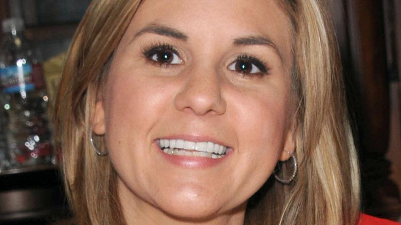Brandi Passante smiling with silver hoop earrings