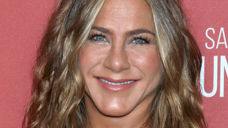 Jennifer Aniston with hair down smiling at camera on red carpet