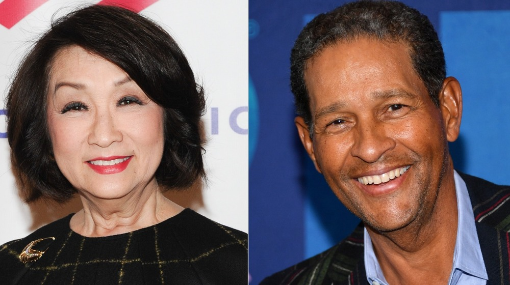 Connie Chung, smiling, black top and red lipstick; Bryant Gumbel smiling, collared shirt, no facial hair