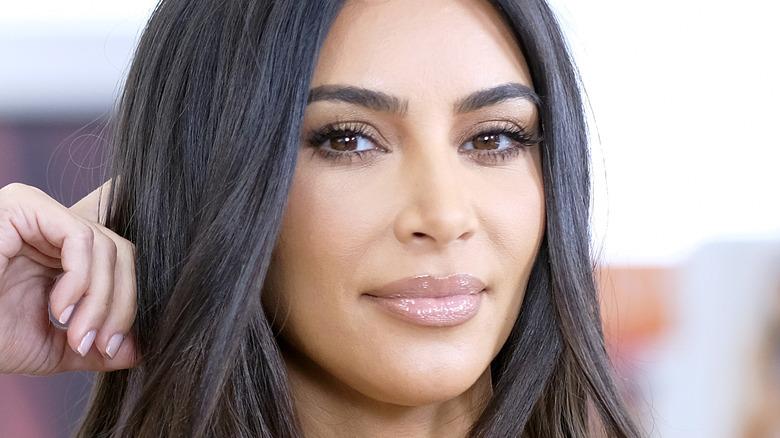 Kim Kardashian poses with hand behind her head.