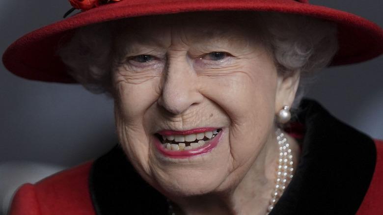Queen Elizabeth smiling in red hat