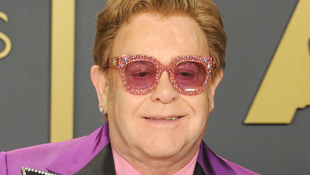 Elton Johns, smiling, Oscars red carpet, 2020, wearing sparkly pink glasses, purple suit