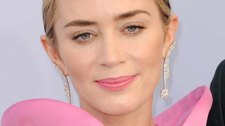Emily Blunt looking at camera with slight smile and pink lipstick