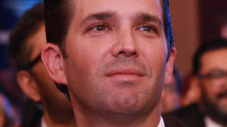 Donald Trump Jr. smiling and looking to side